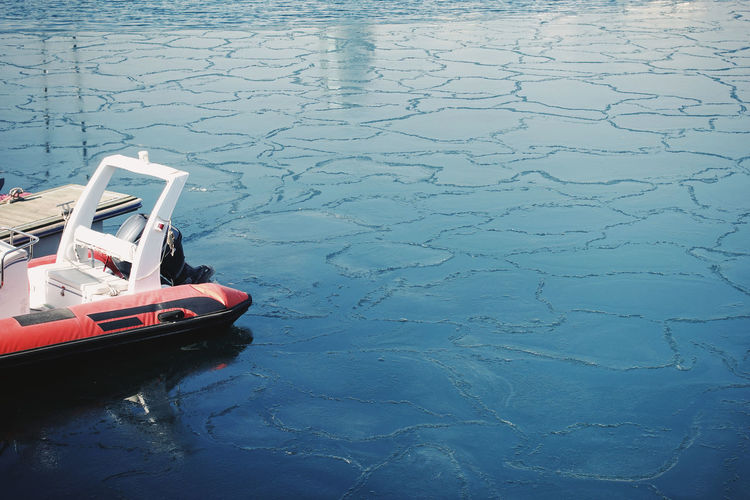 Sea Blue Water Transportation Mode Of Transportation Nature Outdoors Winter Floating Cold Temperature Ice Waterfront Day Reflection Pattern Natural Pattern Boat Sunlight Daylight Coast Port Travel No People Minimalism Minimal