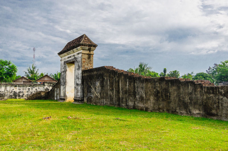 Old building on field against cloudy sky