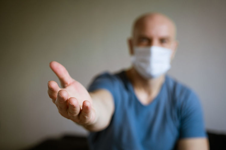 A man in a medical mask pulls his arms forward