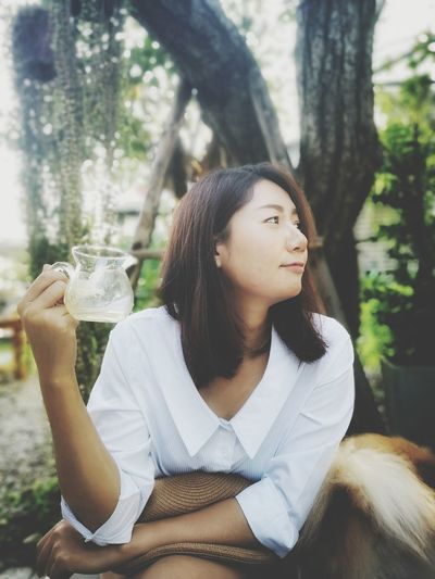 Woman holding drink looking away while sitting against trees in park