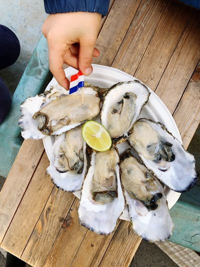 Cropped hand garnishing oysters on table
