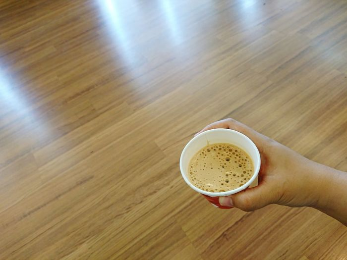 Close-up of hand holding coffee cup on table