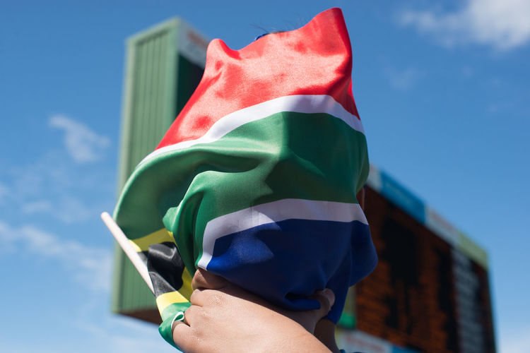 Cropped hands holding south african flag against scoreboard