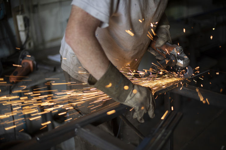 Work grinding machine. sparks from the force of friction. a man in a workshop processes metal.