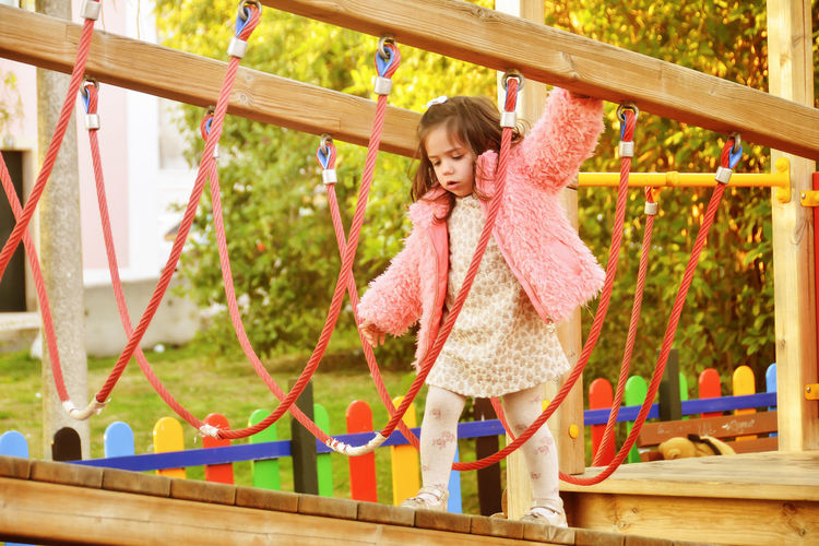 3-4 years girl playing on the city park Casual Clothing Cheerful Childhood Children Only Day Full Length Fun Girls Happiness Jungle Gym Leisure Activity One Girl Only One Person Outdoors People Playground Playing Real People Smiling Warm Clothing