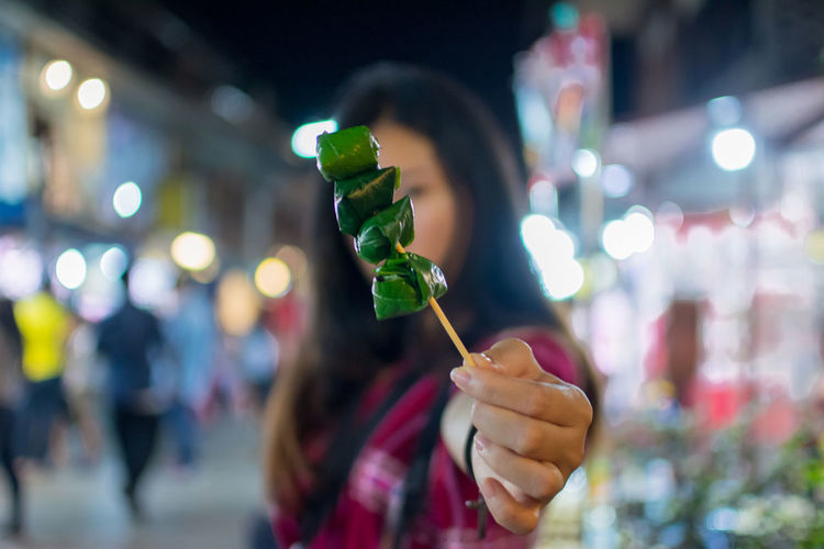 Close-Up Of Woman Holding Food In Skewer At Night