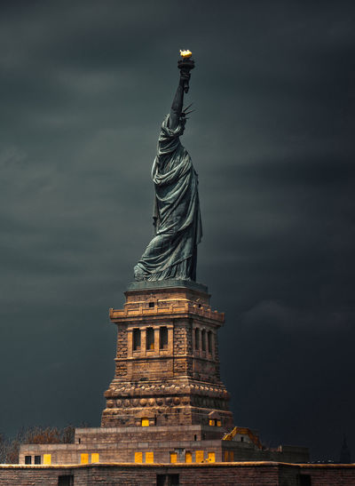 Standing tall - statue of liberty. low angle view of statue against cloudy sky.