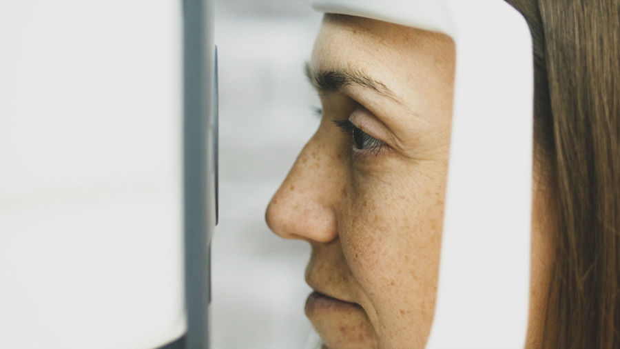 Close-up of woman looking through medical equipment