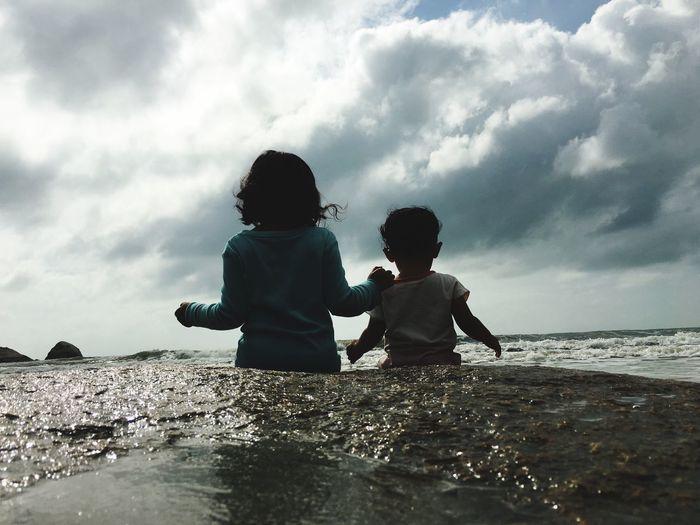 Rear view of siblings in sea against sky