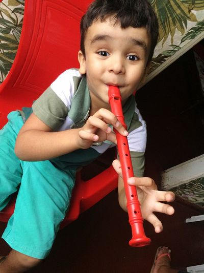 Portrait of cute boy playing flute while sitting on chair