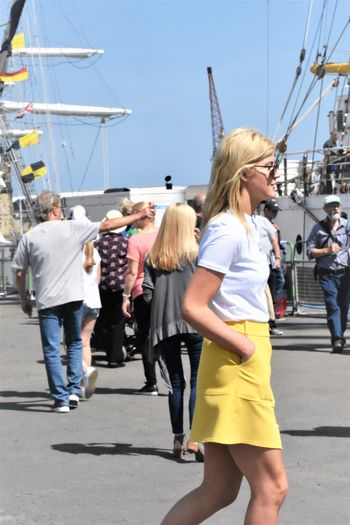 Trendy Toung Female, Slim Wearing A White Top And Yellow Skirt - side view, hand in pocket, while walking Event Nautical Tall Ships Spectators Crowd Of People Yellow Skirt Hand In Pocket Wearing Sunglasses Pretty Young Lady Slim Young Adult Millenial Group Of People Adult City Day Women Hair Casual Clothing Blond Hair Transportation People Walking Clothing Harbor Water Fashion Nautical Vessel