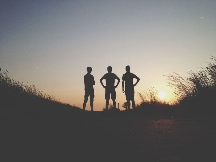 Silhouette male friends standing on field against sky during sunset