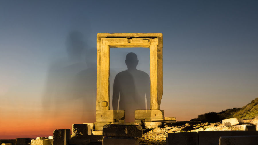 Silhouette of a person vanish through an illuminated ancient gate to space at sunset Destination Afterlife Stargate Transformation Reincarnation Passage Motion Soul Mental Karma Holy Heaven Fantasy Faith Evolution  Eternity Escape Entry Death Dream Concept Dead Gate Ancient Spirituality