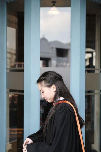 Portrait of woman standing against built structure