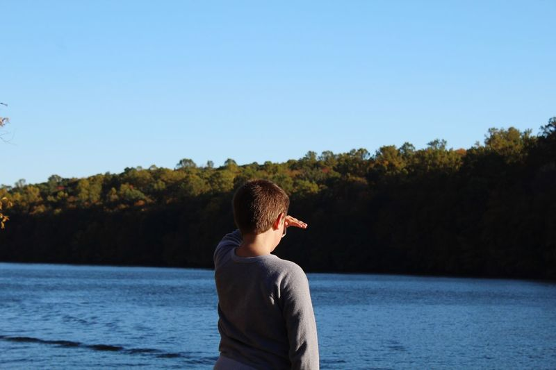 Rear view of boy shielding eyes while standing by river against clear sky