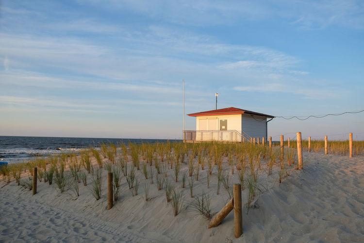 Hut on beach by sea against sky