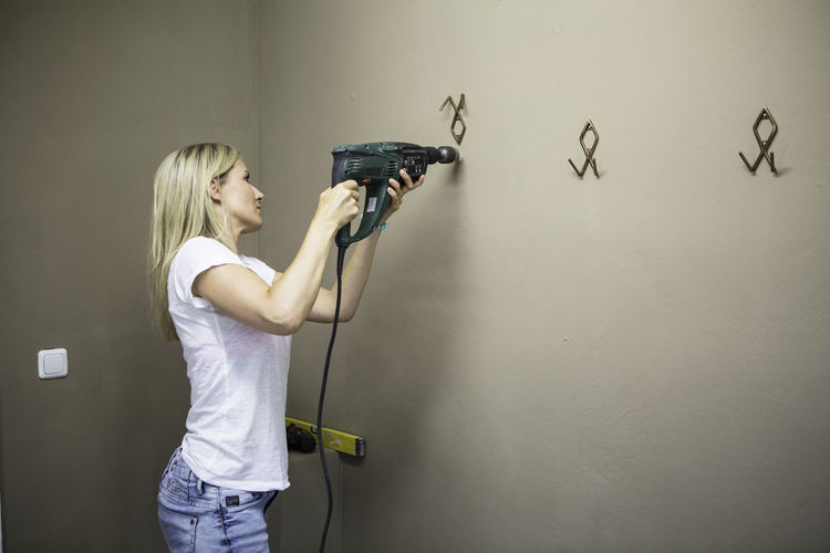 Woman drilling wall