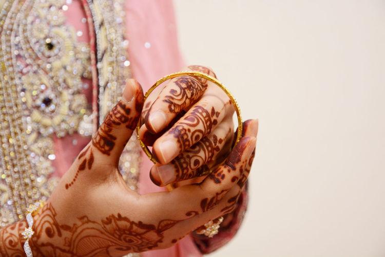 Bride wearing bangles in tattooed hand