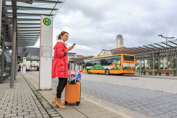 A young woman at bus and rail station in Sonneberg, Germany City, Town, Adults, Bag, Baggage, Bus Station, Business, Europe, Female, Job, Journey, People, Phone, Portrait, Rail Station, Shopping, Street, Suitcase, Traffic, Train, Train Station, Traveling, Urban, Waiting, Women, Young Mode Of Transportation Transportation City Architecture Day One Person Real People Adult Women Building Exterior