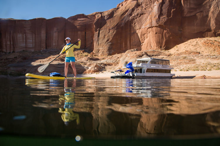 A women is stand up paddle boarding on Lake Powell in Utah near an anchored houseboat on a beach. Water Rock - Object Waterfront Lifestyles Rock Formation Rock One Person Leisure Activity Women Full Length Paddle Boarding Stand Up Paddle Boarding Lake Powell Houseboat Fun House Plant Boat Watersports Real People