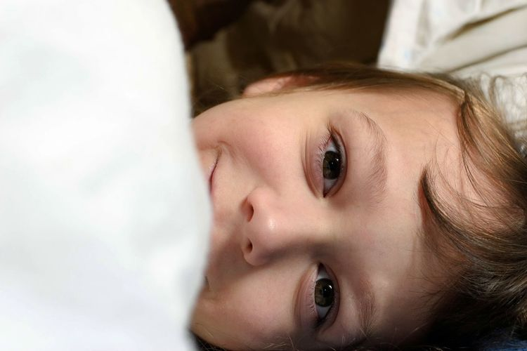Close-up portrait of cute baby lying on bed