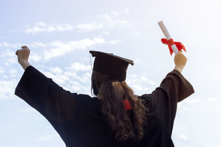 Rear view of woman in graduation gown standing with arms outstretched against sky