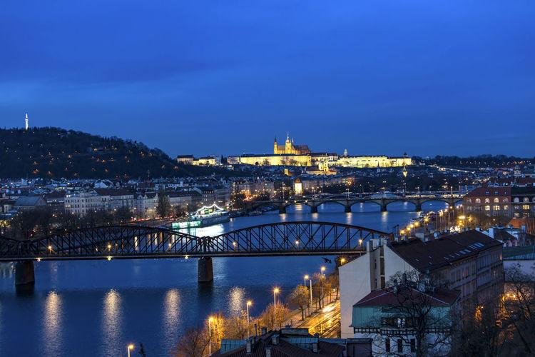 Bridges over vltava river in city against sky at night