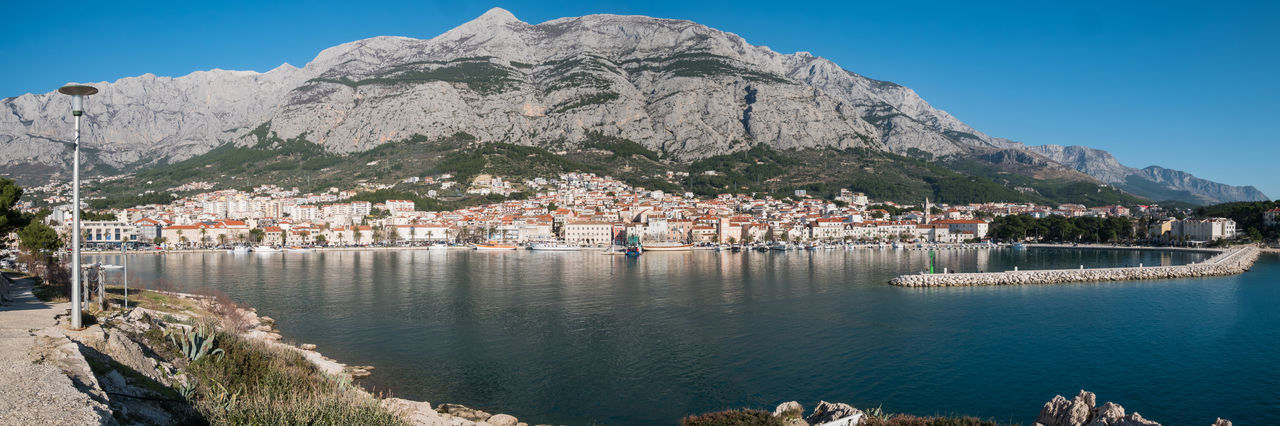 Makarska city panorama from the sea on sunny summer day Panorama Makarska Makarska Riviera Dalmatia Croatia Europe Adriatic Sea Mediterranean  Landscape City Town Sea Port Harbor Mountain Biokovo Scenics Summer Travel Tourism Vacations Water Architecture Built Structure Nautical Vessel Sky Day Mountain Range Outdoors No People Sunny