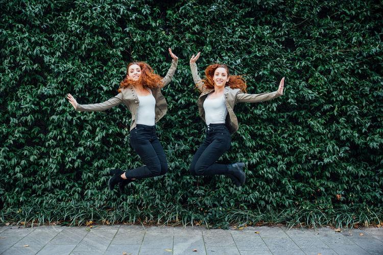 Full length portrait of siblings jumping against plants