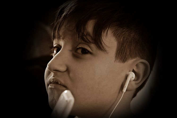 Close-up of boy making face while listening music