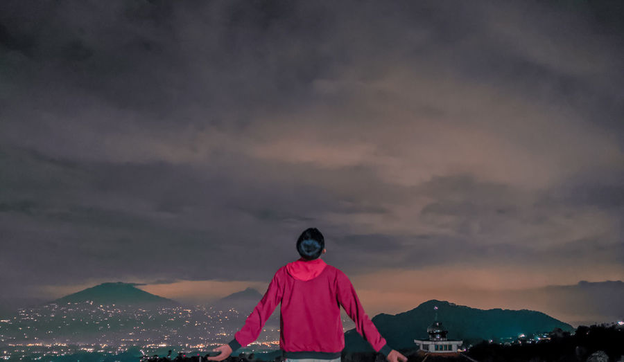 Rear view of woman standing on mountain against sky during sunset