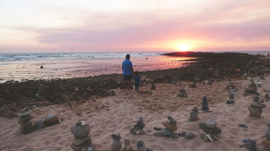 Rear view of father standing with daughter by stacked stones at beach during sunset