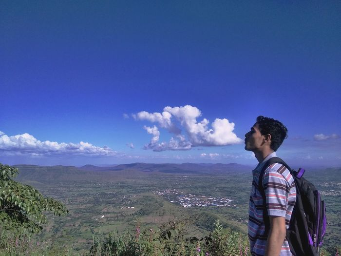 Young man looking at mountain against sky