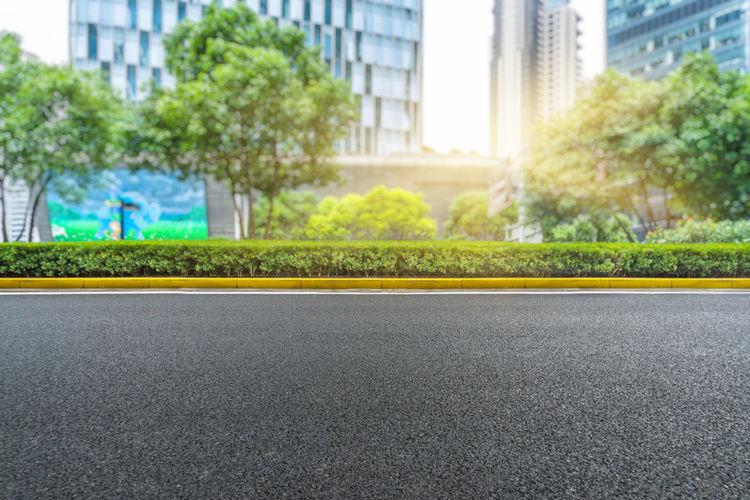 Empty road by buildings in city