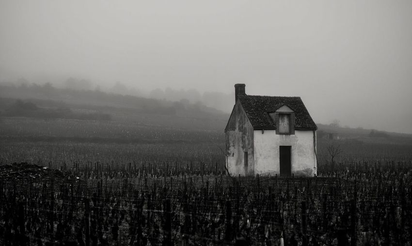 Old house on field against sky during foggy weather