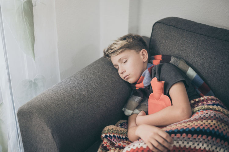 High angle view of boy sleeping with hot water bottle on sofa at home