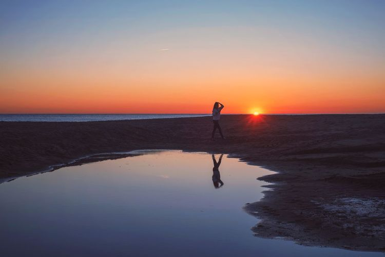 Silhouette person standing on beach during sunset