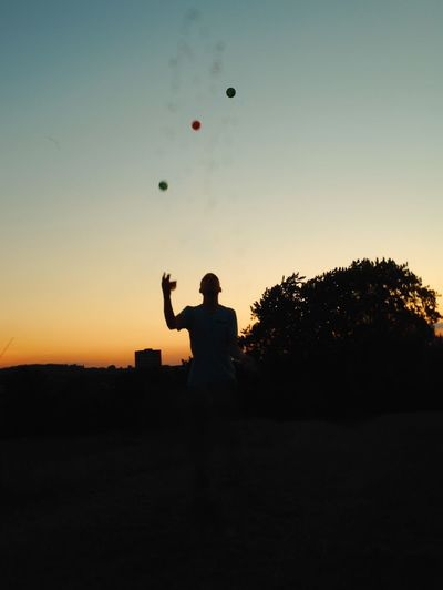 Silhouette Boy Playing With Balls On Field Against Sky During Sunset