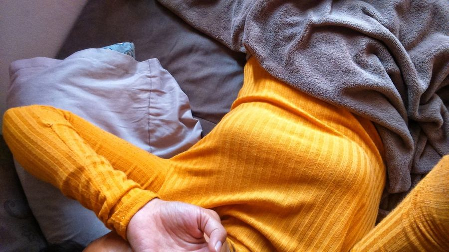 Midsection Of Woman Lying On Bed At Home