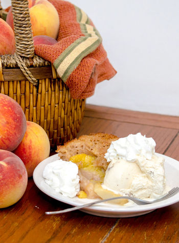 A basket of fresh peaches rests next to fresh made peach cobbler, topped with ice cream and whipped topping Agriculture Dessert Fresh Produce Hello World Nature Orange Summertime USA Vitamins Food Fresh Fruit Ice Cream Juicy Just Picked Michigan Peaches Natura' Organic Peach Peach Cobbler Peaches Produce Sweet Tasty Yellow