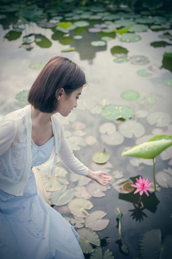 A beautiful young woman sitting besides the lotus. One Person Women Real People Lifestyles Leisure Activity Three Quarter Length Plant Young Women Young Adult Flower Standing Flowering Plant Looking Water Beauty Beauty In Nature Casual Clothing Beautiful Woman Hairstyle Outdoors Lotus