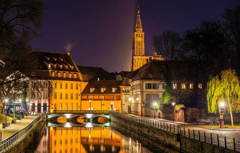 Illuminated bridge by buildings against sky at night