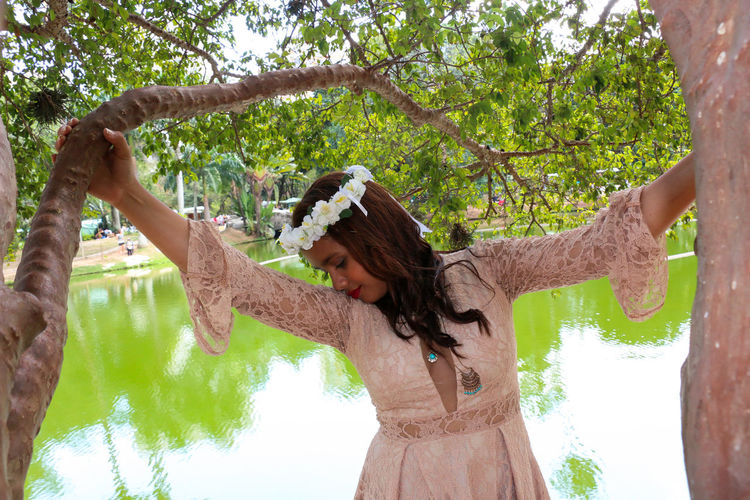 Woman Wearing Flowers While Standing By Trees Against Lake