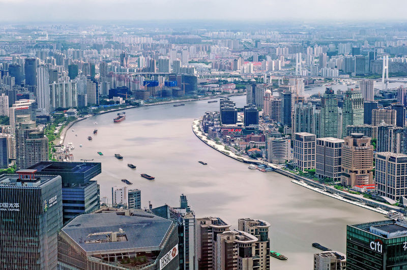 Aerial view of river amidst modern buildings in city