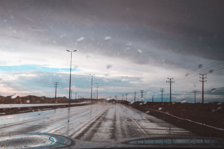 Road against sky seen through windshield during rainy season