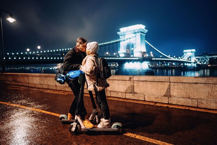 Couple kissing on bridge in city at night