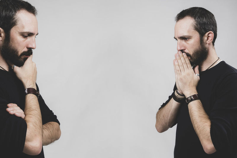 Bearded worried man Beard Facial Hair Young Men Two People Men Indoors  Young Adult Standing Mid Adult Mid Adult Men People Front View Adult Real People Hand Wall - Building Feature Studio Shot Waist Up White Background Couple - Relationship Contemplation