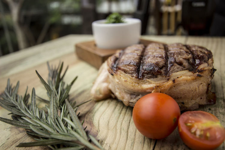 Close-up of tenderloin steak by rosemary on wooden table