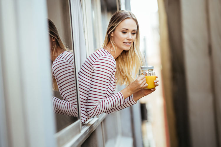 Young woman holding drink out of window