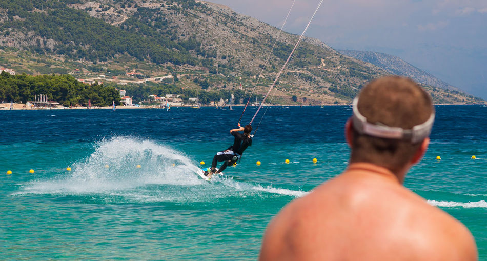Rear View Of Male Looking At Man Kiteboarding In Sea